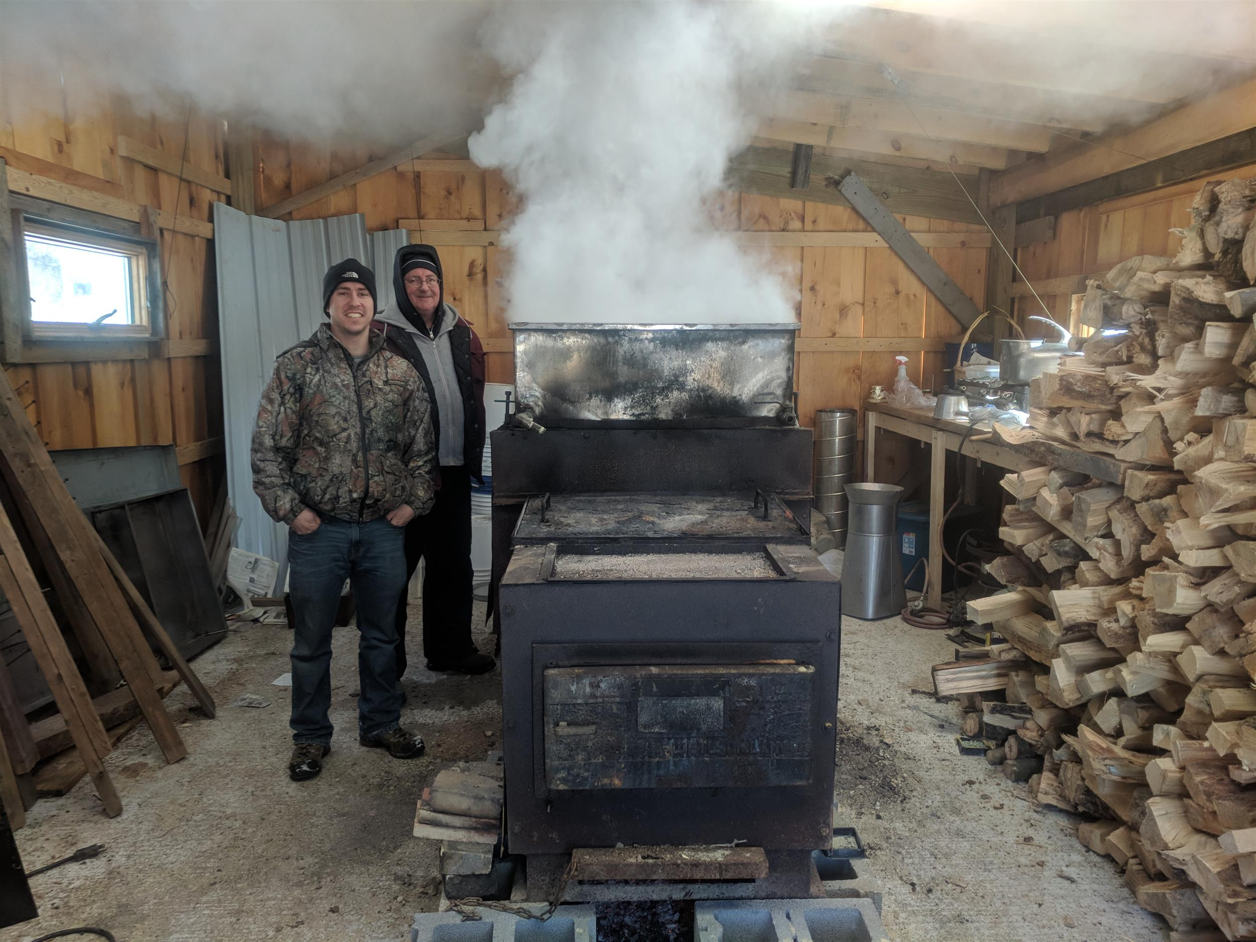2 Men near a steamy Maple Syrup evaporator